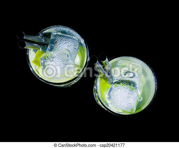 top of view of glasses with cocktail and ice with lime slice on black background