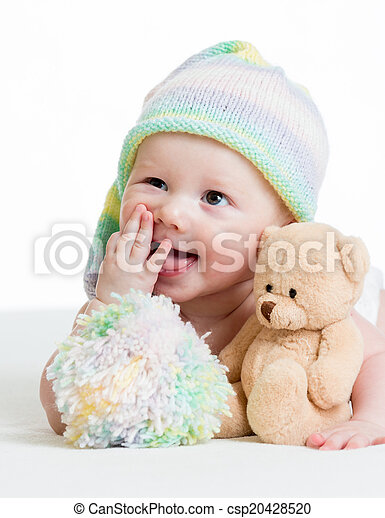 funny baby boy lying on bed with plush toy - csp20428520