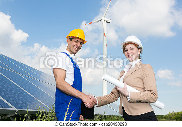 Engineers shake hands in front of solar panels and wind turbine - csp20430293