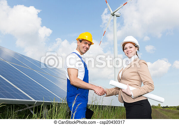 Engineers shake hands in front of solar panels and wind turbine - csp20430317