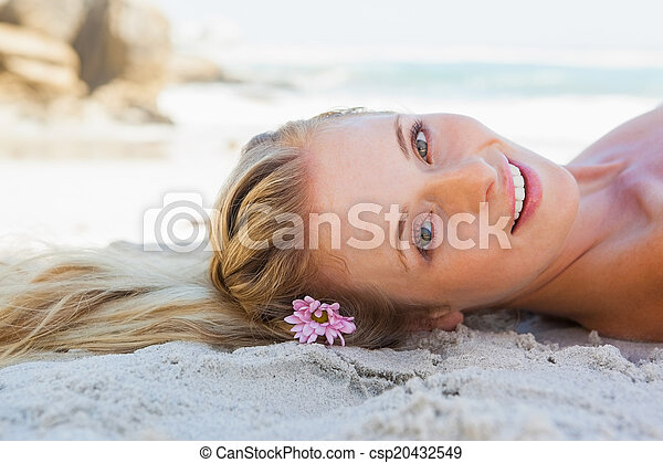 Pretty carefree blonde lying on the beach - csp20432549