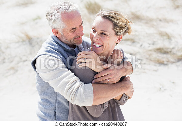 Happy hugging couple on the beach looking at each other - csp20440267
