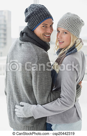 Cute couple in warm clothing hugging smiling at camera