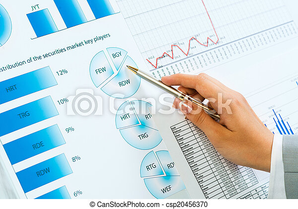 female hand pointing pen on financial charts - csp20456370
