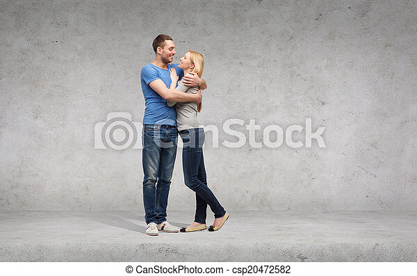 smiling couple hugging and looking at each other - csp20472582
