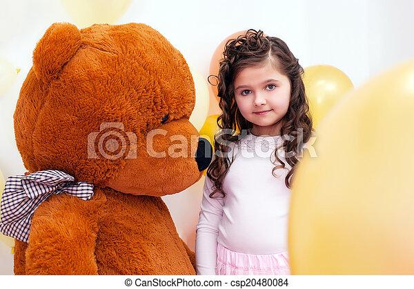 Cute little brunette posing with big teddy bear