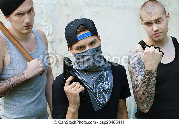 three gangsters with weapons looking into camera. criminals holding baseball bat, gun and knuckles