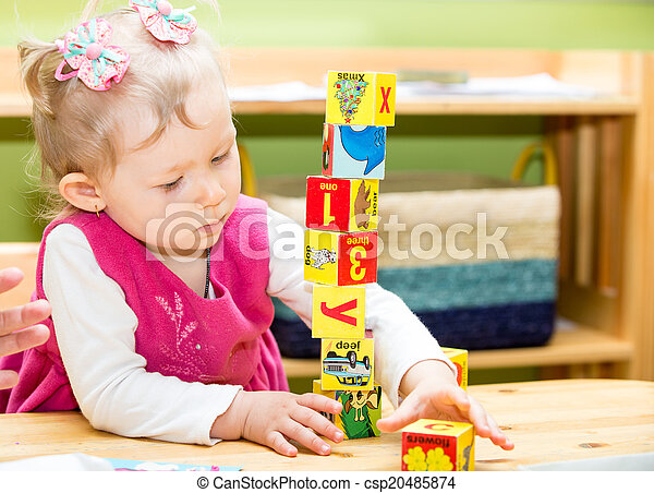 Little child girl playing with toy letter and number blocks  in kindergarten in Montessori preschool Class. - csp20485874