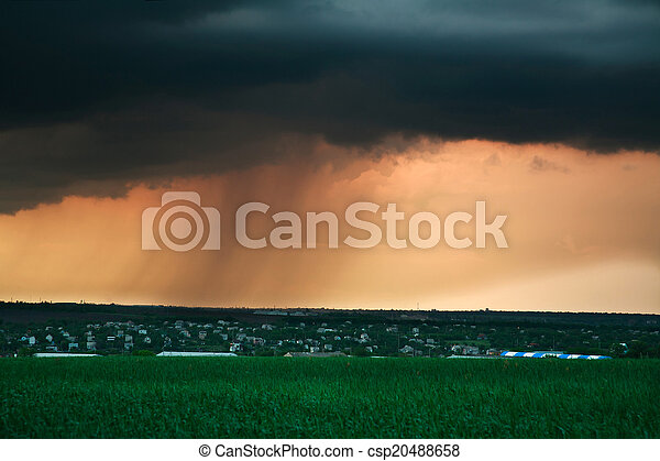 Storm cloud with rain at sunset, above the village, rural landscape weather