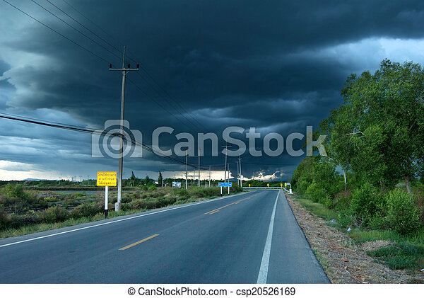 countryside road and dark storm clouds