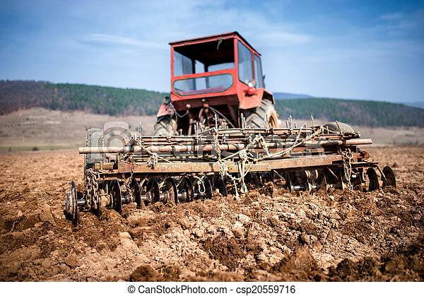 Tractor at farm working and plowing the field. Agriculture - csp20559716