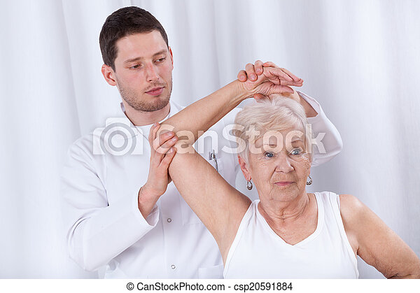 Physiotherapist rehabilitating elderly woman - csp20591884