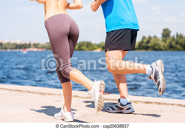 Jogging together. Close-up of young woman and man in sports clothing running along the riverbank