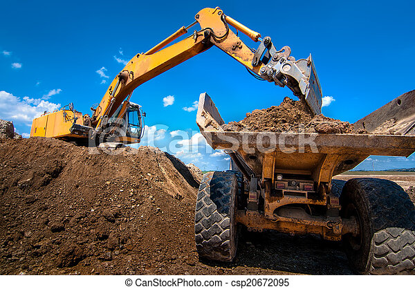 Yellow excavator loading soil into a dumper truck