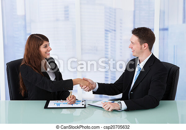 Business People Shaking Hands At Office Desk - csp20705632