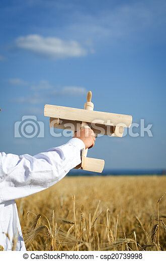 Little boy playing in farmland with a toy airplane - csp20739998