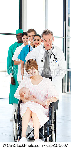 Doctors attending to a patient and her newborn baby - csp2075007