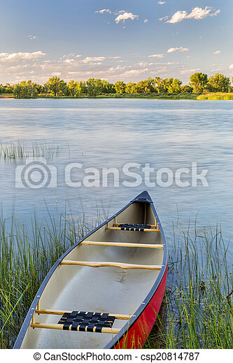 red canoe on lake ready for paddling - csp20814787