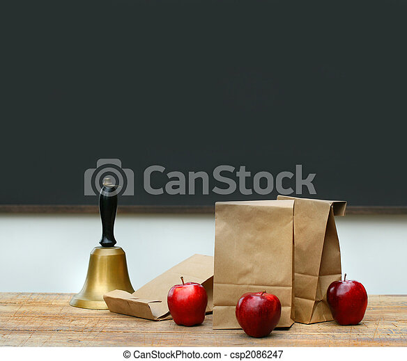 Lunch bags with apples and school bell on desk - csp2086247