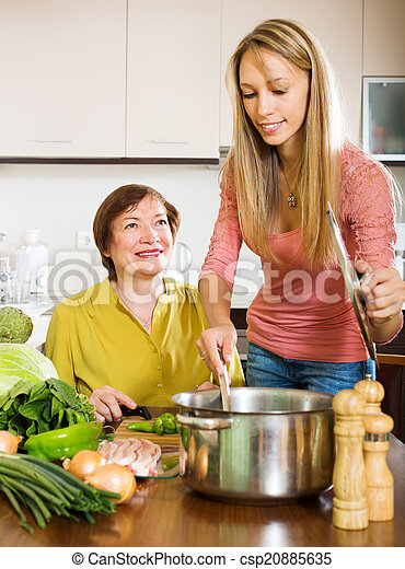 Happy mature woman with adult daughter cooking  together  - csp20885635