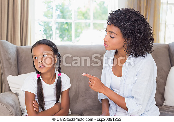 Pretty mother sitting on couch scolding her daughter