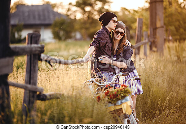 Two beautiful hipsters standing outdoor in summer with white vintage fixed gear bicycle - csp20946143