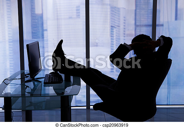 Relaxed Businessman Sitting At Computer Desk In Office - csp20963919