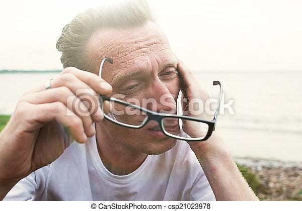 Man rub tired eyes on the beach