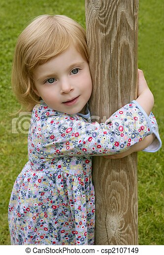 Beautiful little toddler girl hug a trunk - csp2107149