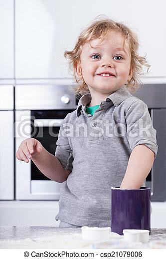 Child having good time in kitchen - csp21079006