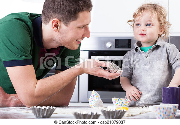 Father helping son baking muffins - csp21079037