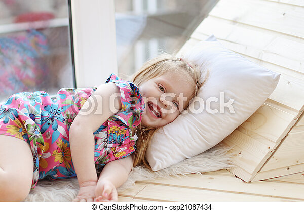 Pretty little blonde girl laughs and lies on white pillow