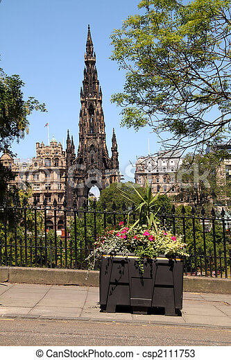 The Scott Monument on Edinburgh\'s Princes Street with a colourful floral tub in the foreground.
