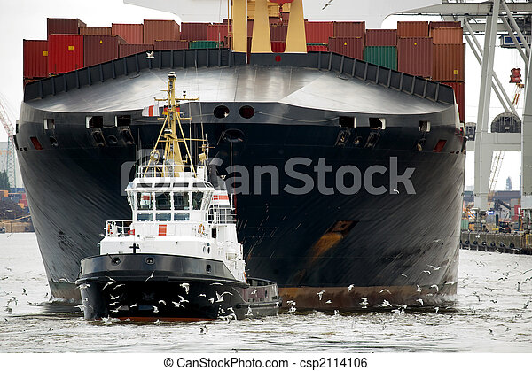 tugboat towing freighter in harbor - csp2114106