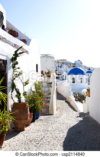 incredible santorini with cobble stone street flowers and classic whitewashed cyclades architecture with blue dome greek church in oia on the famous island of santorini thira in greece - csp2114840
