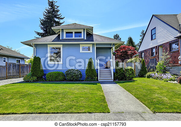 House exterior in light blue. View of front yard and entrance po