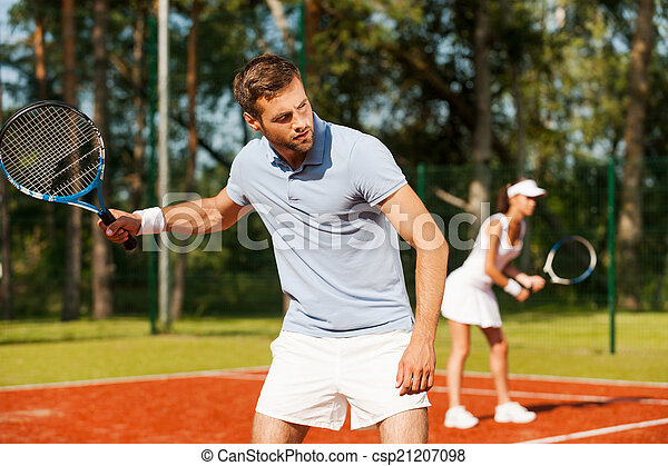 Playing as one team. Handsome young man holding tennis racket and looking away while standing on tennis court and with woman in the background