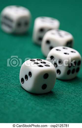 Gambling die on a green surface. - csp2125781