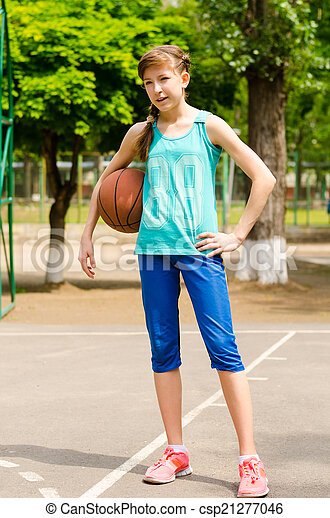 Beautiful smiling girl standing with a basketball in outdoor basketball court