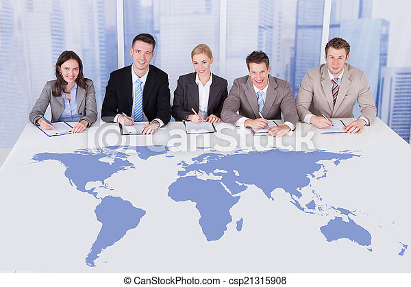 Business People Sitting At Conference Table With World Map