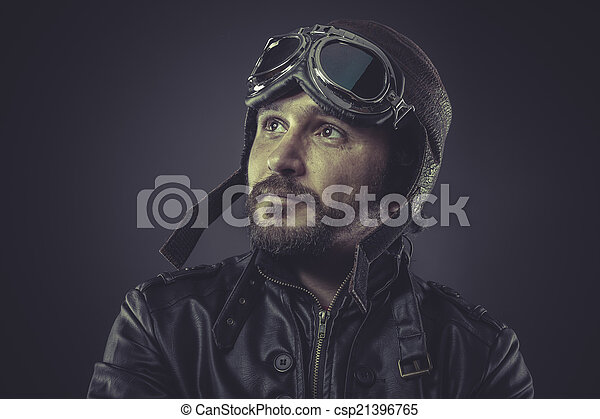 wartime pilot dressed in vintage style leather cap and goggles - csp21396765