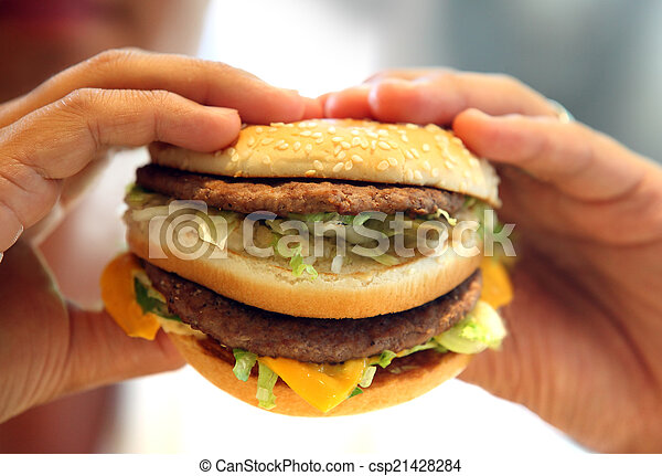 man\'s hands, holding onto a burger