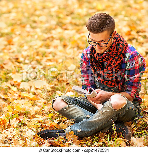 Young hipster relaxed man reading book in nature, back on tree
