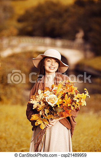 Young woman walking in autumn park with a bouquet of fall leav