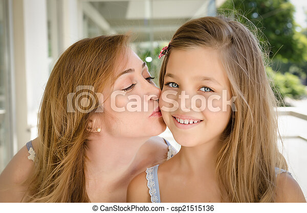 Mother kissing her daughter in the cheek.