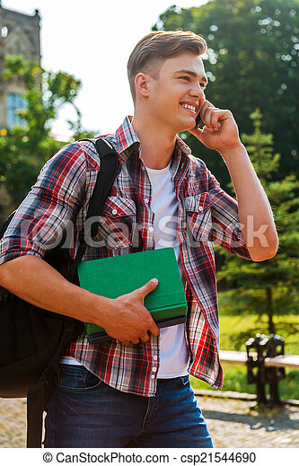 In touch with his friends. Handsome male student talking on the mobile phone and smiling while walking outdoors