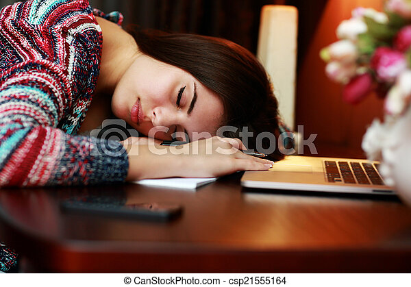 Tired woman sleeping on the table at home
