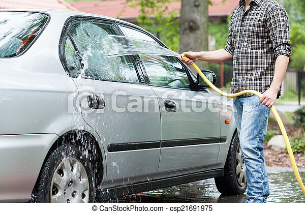 Man rinsing foam from car