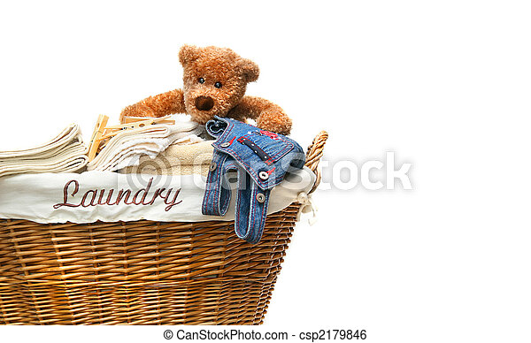 Laundry basket full of towels with teddy bear on white - csp2179846