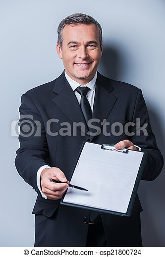 I need your signature here. Portrait of confident mature man in formalwear stretching out clipboard with paper and pointing it with pen while standing against grey background